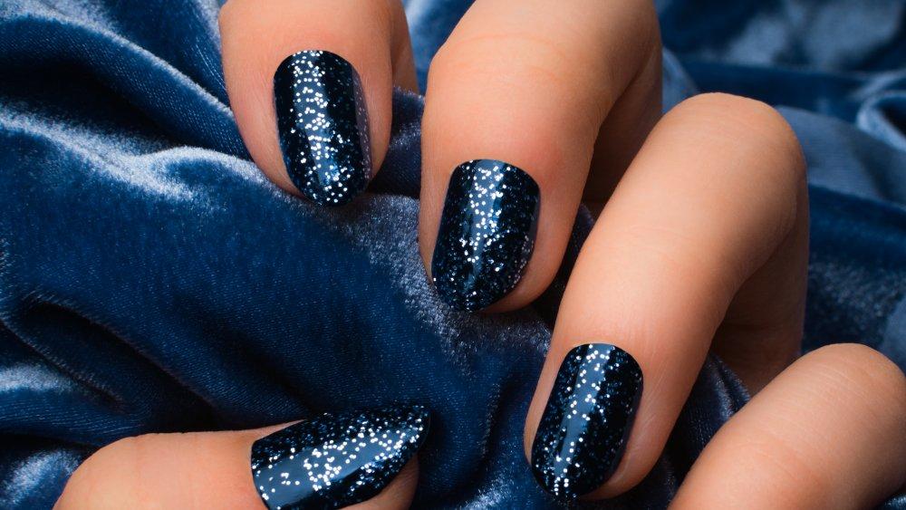 A woman's hand with dark blue nail polish