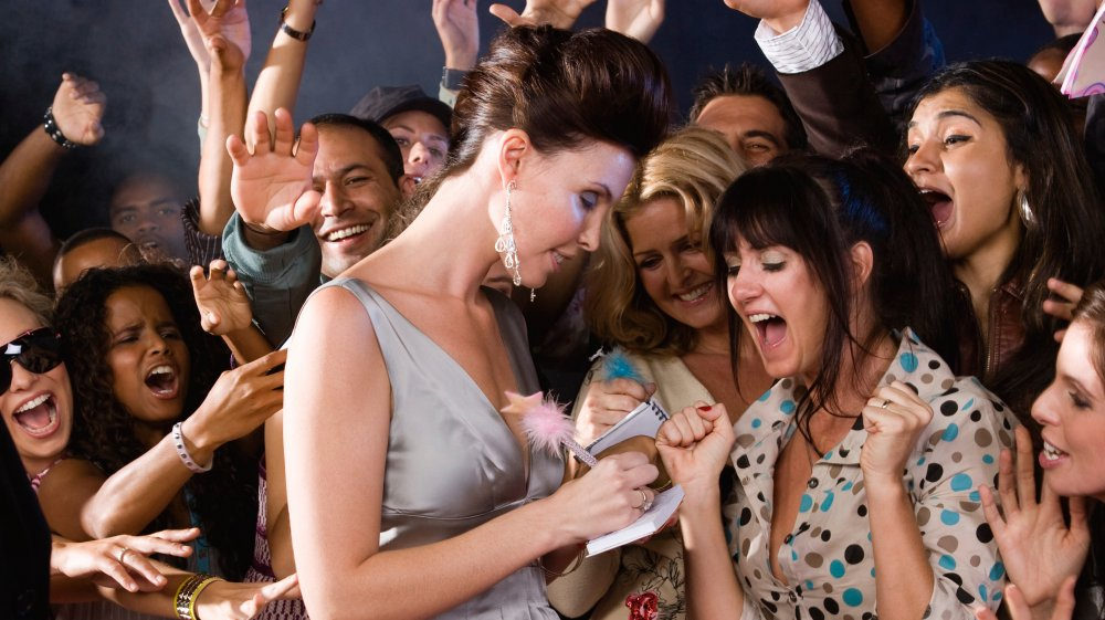 A celebrity signing autographs for screaming fans