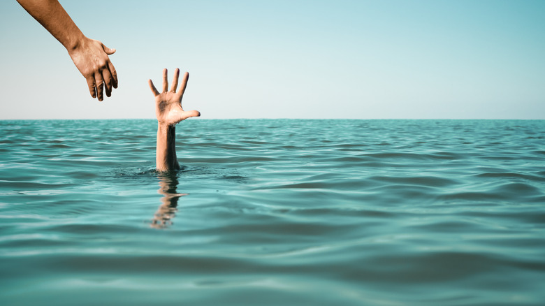 person drowning, reaching for help