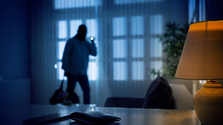 Intruder with a flashlight in a living room