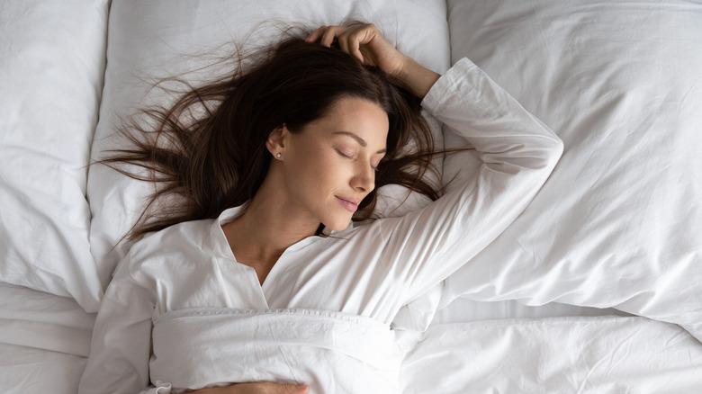 Woman sleeping against white linen