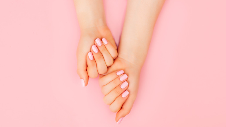 Two hands closed showing pink fingernails on a pink background