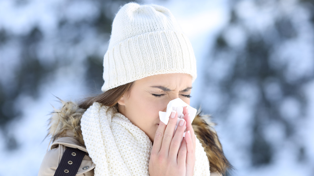 Woman with a cold nose in the snow