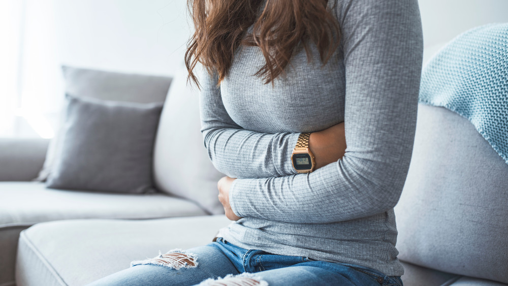 Woman holding her abdominal area during cramps