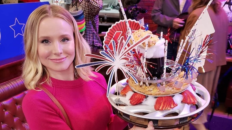 Kristen Bell with a prop on The Good Place set