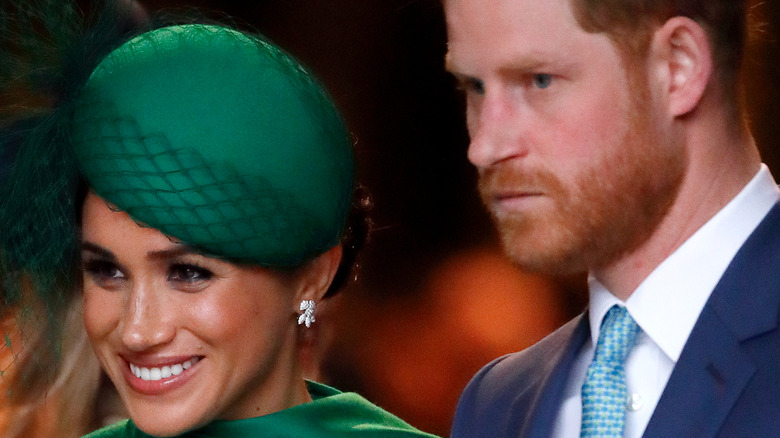 Prince Harry and Meghan Markle smiling in green hat