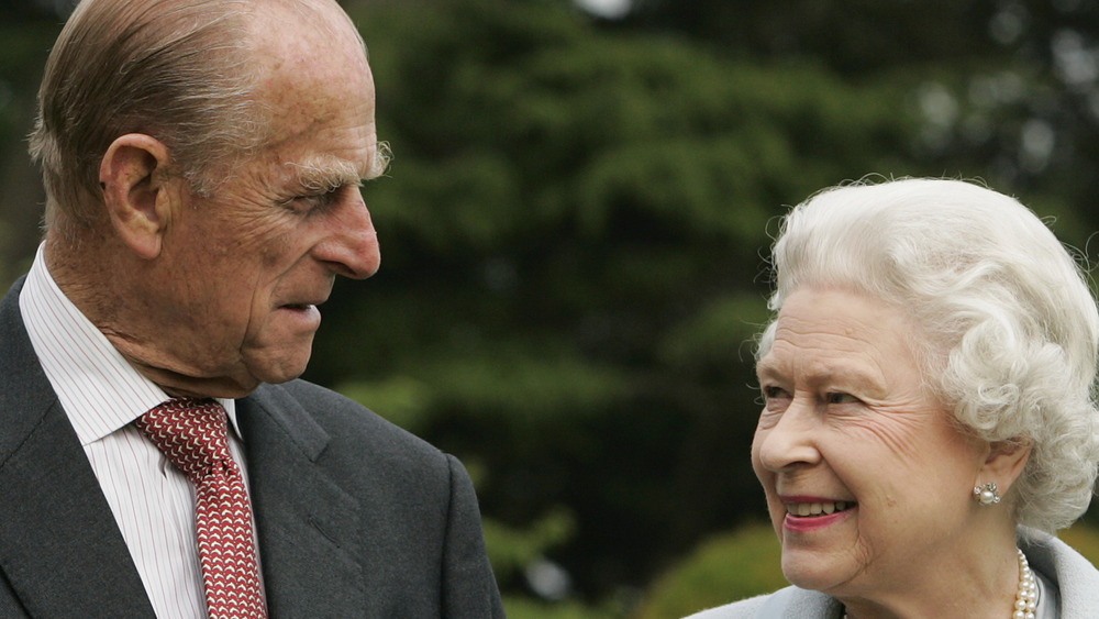 Queen Elizabeth and Prince Philip smiling at each other