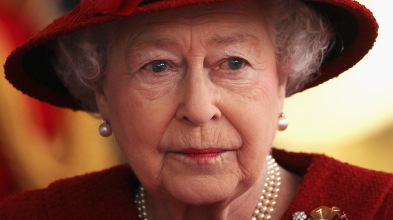 Queen Elizabeth looking to the side wearing red hat