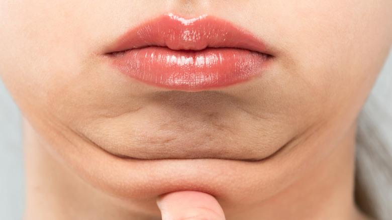 Woman putting thumb on chin
