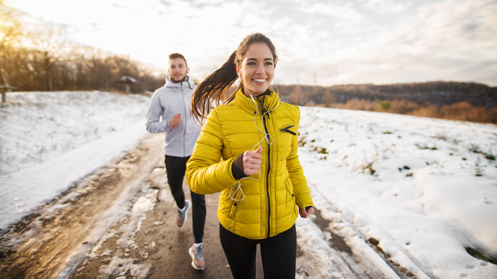 Woman in yellow jacket and man running in the snow