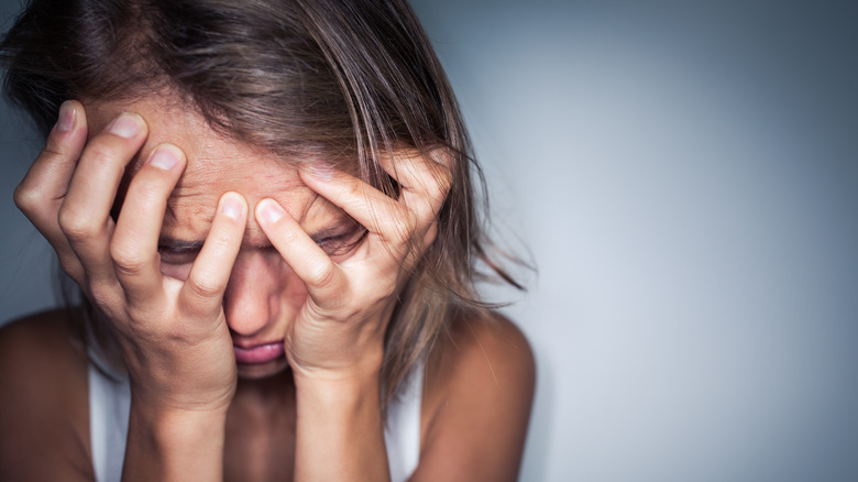 woman covering her face upset