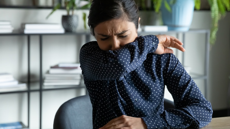 Woman coughing into sleeve