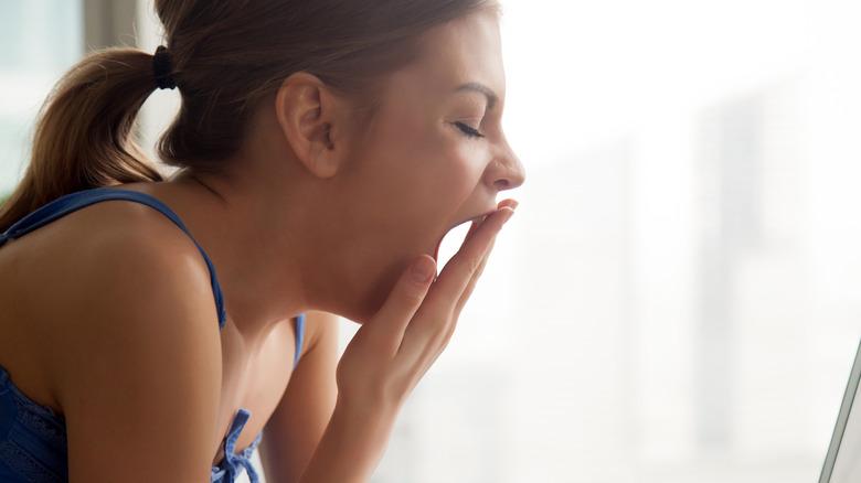 Yawning woman working at computer