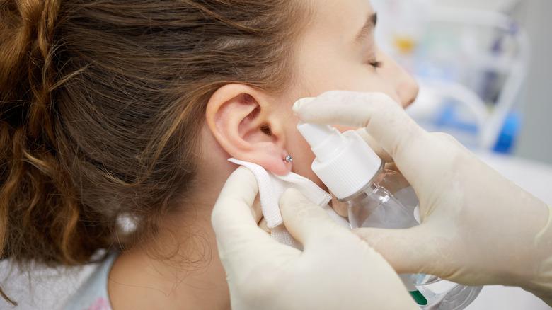 Girl sanitizing her ear piercing
