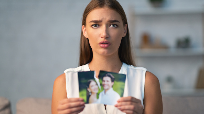 woman holding torn photo