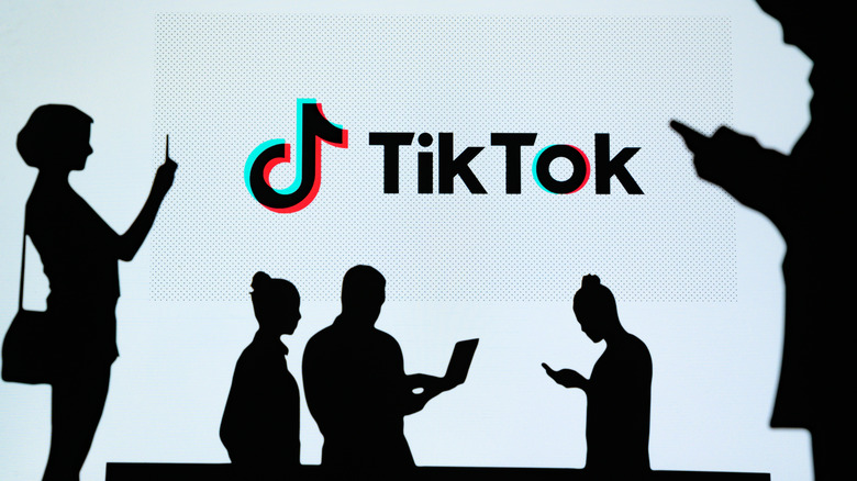 TikTok logo and a silhouettes people looking at their phones.