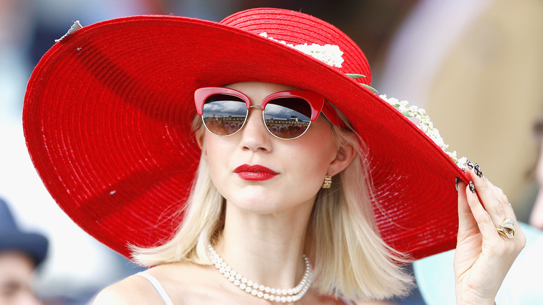 Blonde woman wearing big red hat at the Kentucky Derby