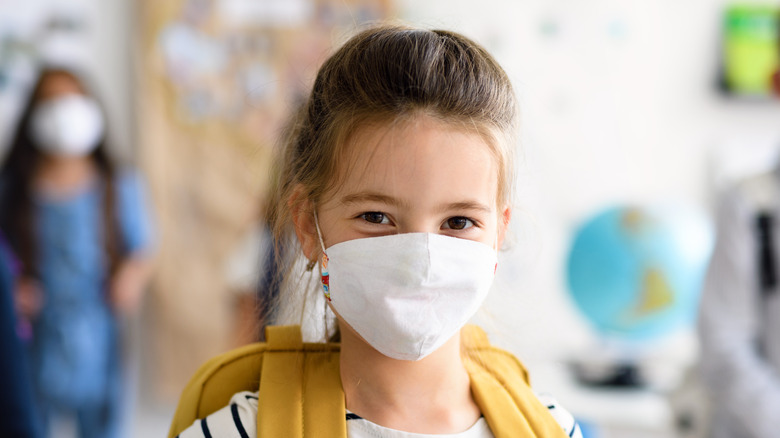 Girl wearing mask and backpack