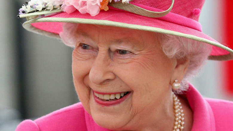 The Queen smiling in a pink hat
