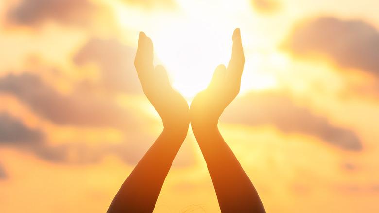 Hands against sunset