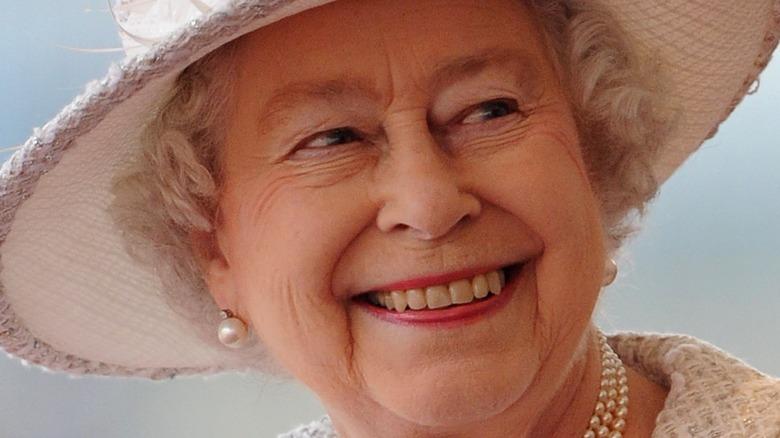 Queen Elizabeth II smiling in white