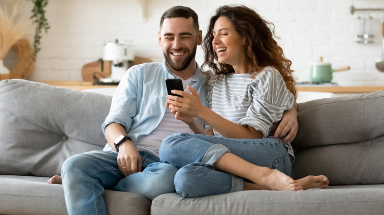A couple laughs on the couch at their phone