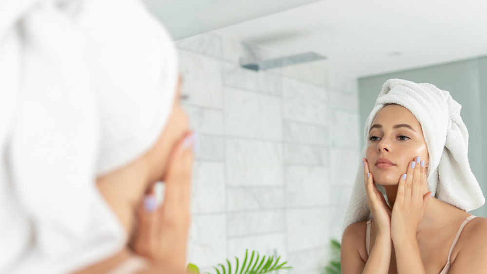 A woman applying lotion to her face in the mirror