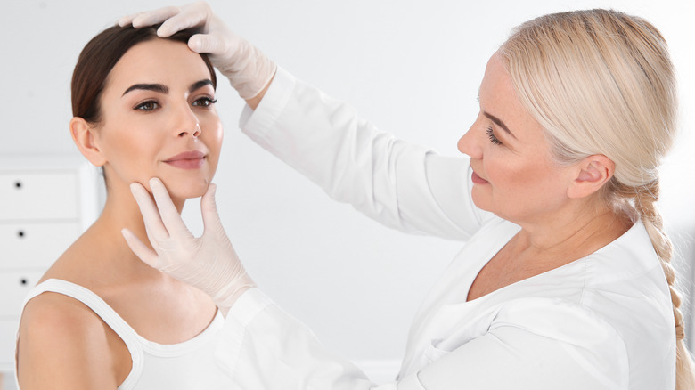 Dermatologist examining woman's mole