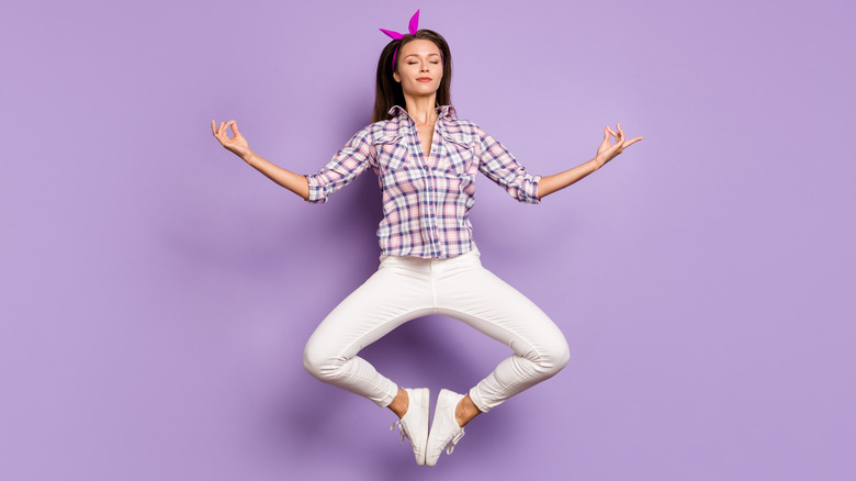 woman jumping against violet background