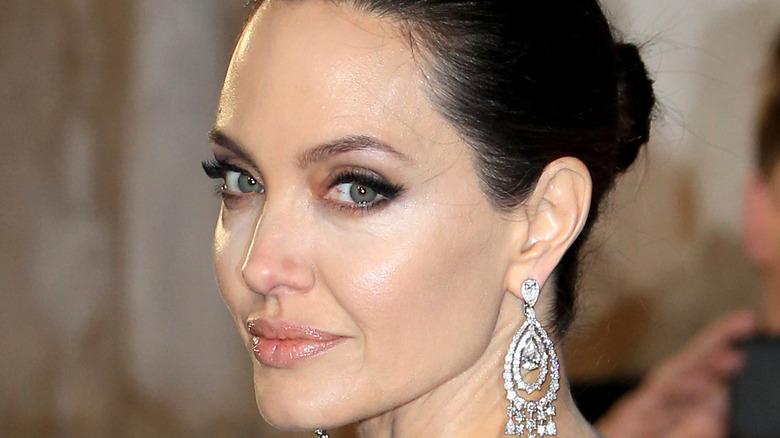 Angelina Jolie wears a black dress on the red carpet.