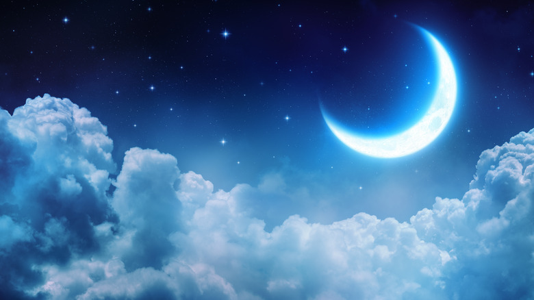 Moon and stars over clouds
