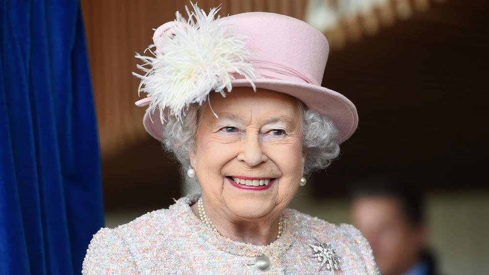 Queen Elizabeth smiling in pink hat