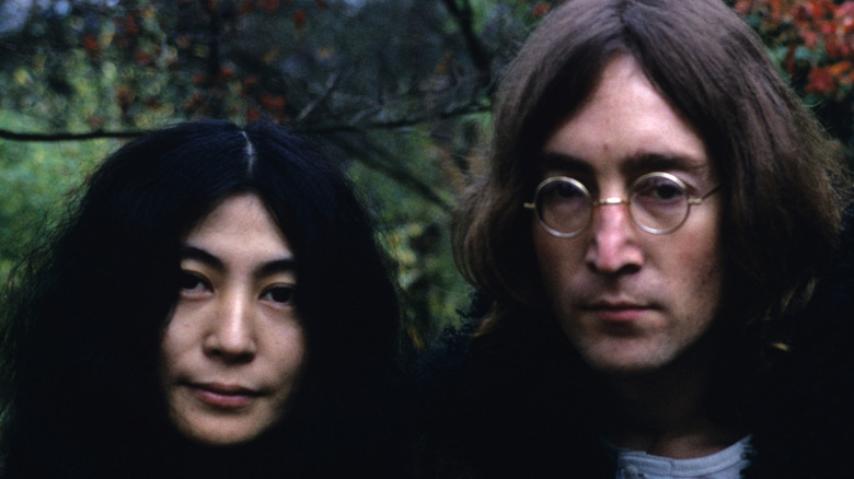 Yoko Ono and John Lennon standing in a forest