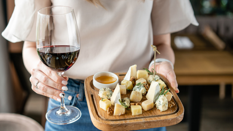 Person holding wine and cheese