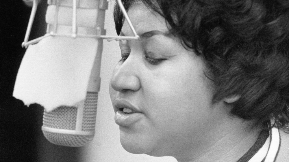 Aretha Franklin singing into microphone