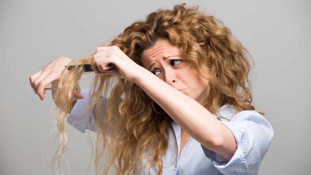 Woman cutting her long hair