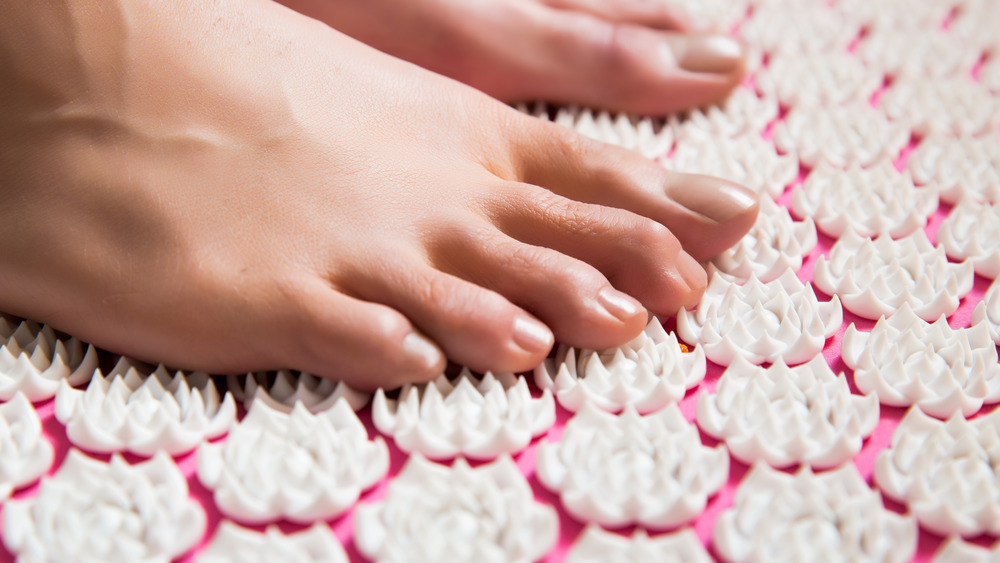 Person stepping on acupressure mat
