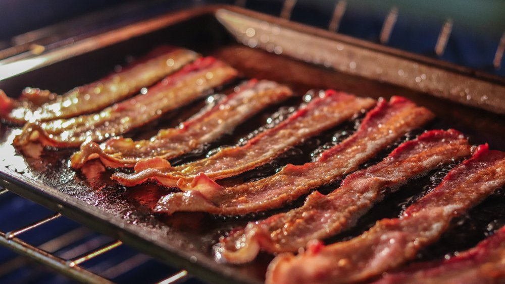 Bacon cooking on a baking sheet in the oven