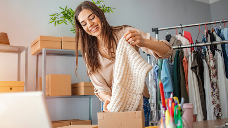 Woman packing clothes into brown box