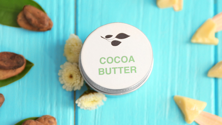 A jar of cocoa butter with cocoa solids around it