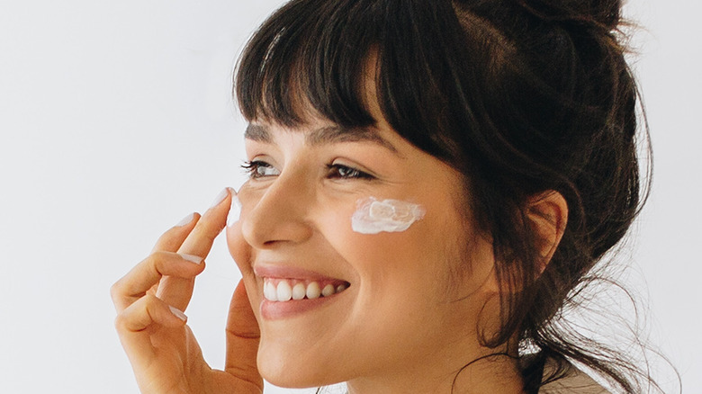 A woman smiling while applying moisturizer on her face.