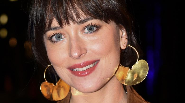Dakota Johnson smiling, wearing earrings