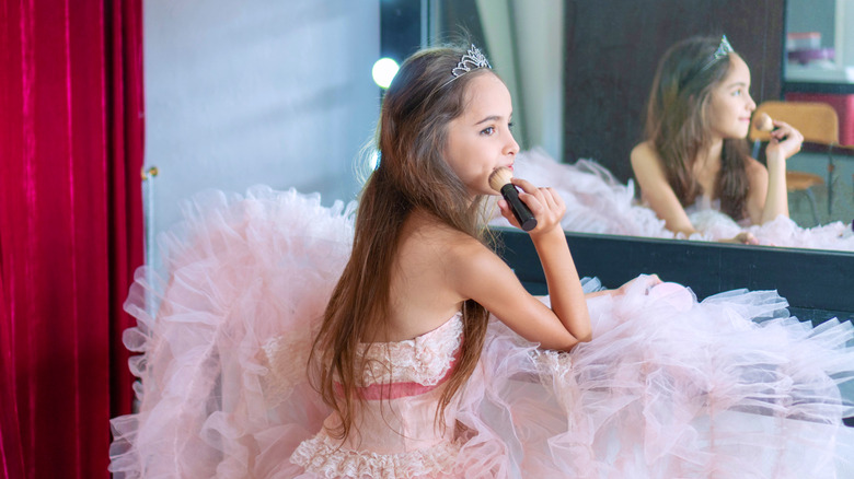 A young girl in a pink dress puts on makeup.