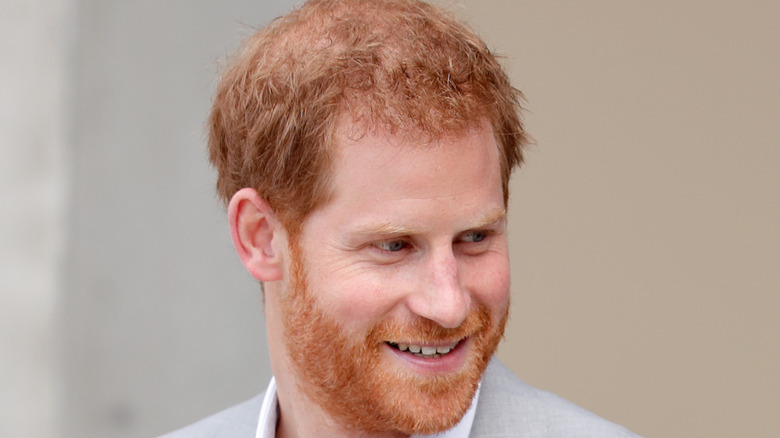 Prince Harry smiles will looking to the side.