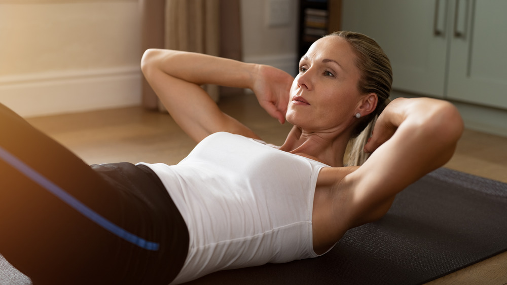 Woman doing crunches on a yoga mat