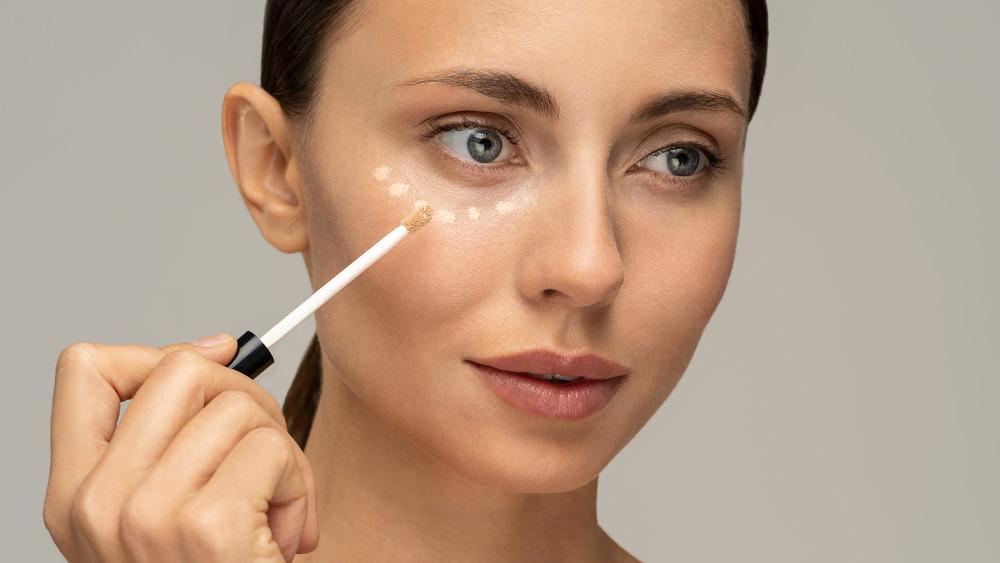 Woman putting on makeup.