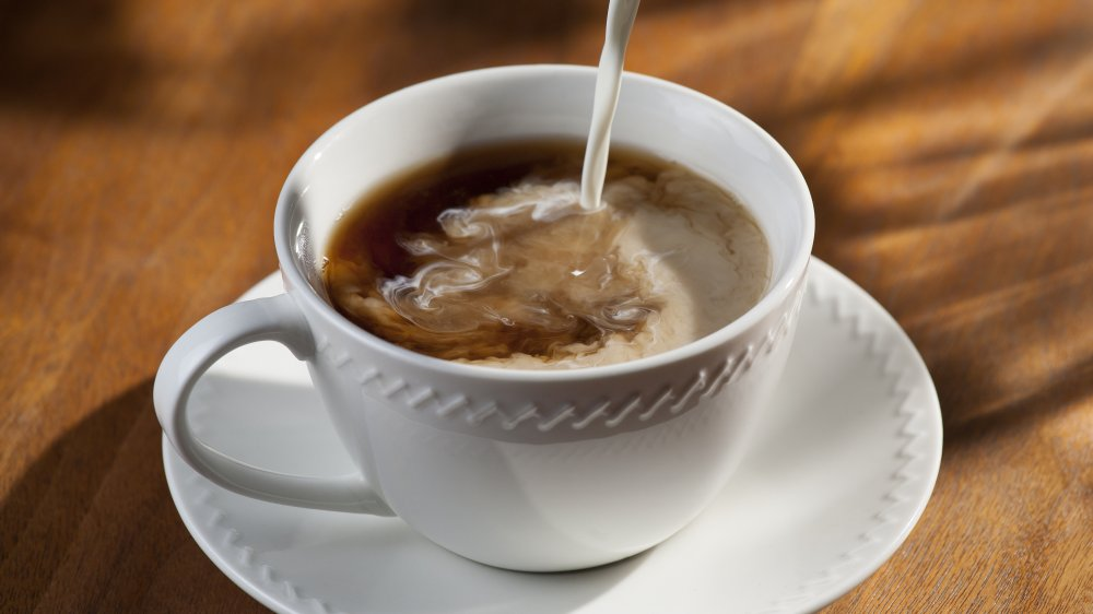 Creamer being poured into a cup of coffee