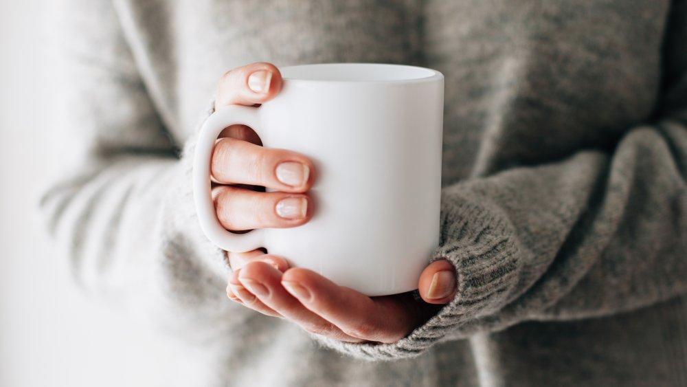 woman holding a mug of hot water