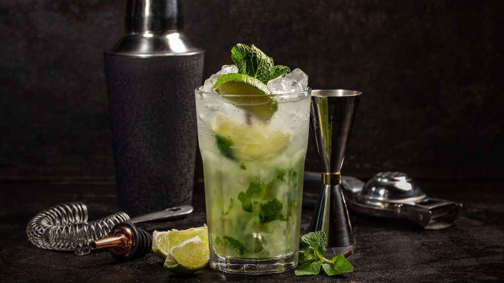 A mojito made with rum on a bar with ingredients and accessories