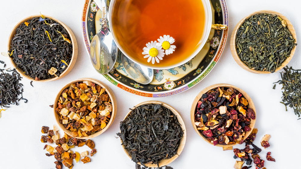 Cup of tea surrounded by dry tea leaves